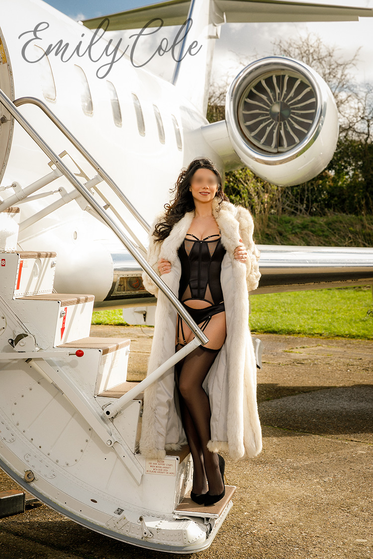 Escort Emily posing in lingerie and fur coat, next to a private jet on an airfield just outside of London.