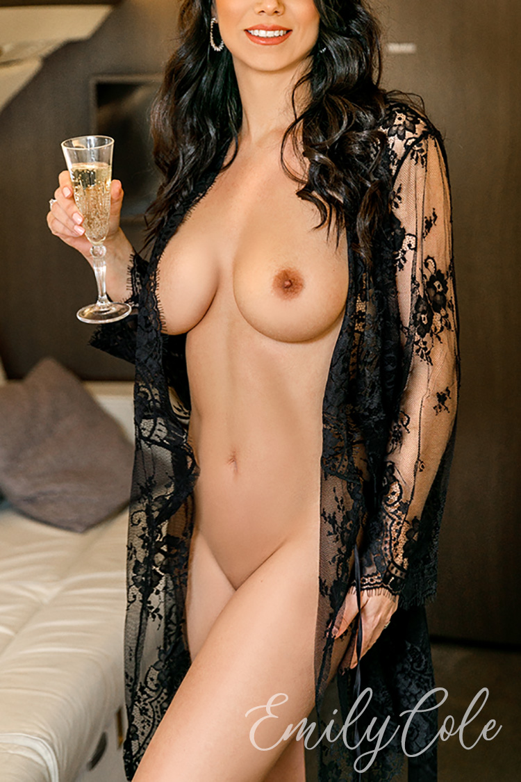 Busty escort posing in a black gown with the glass of champagne.