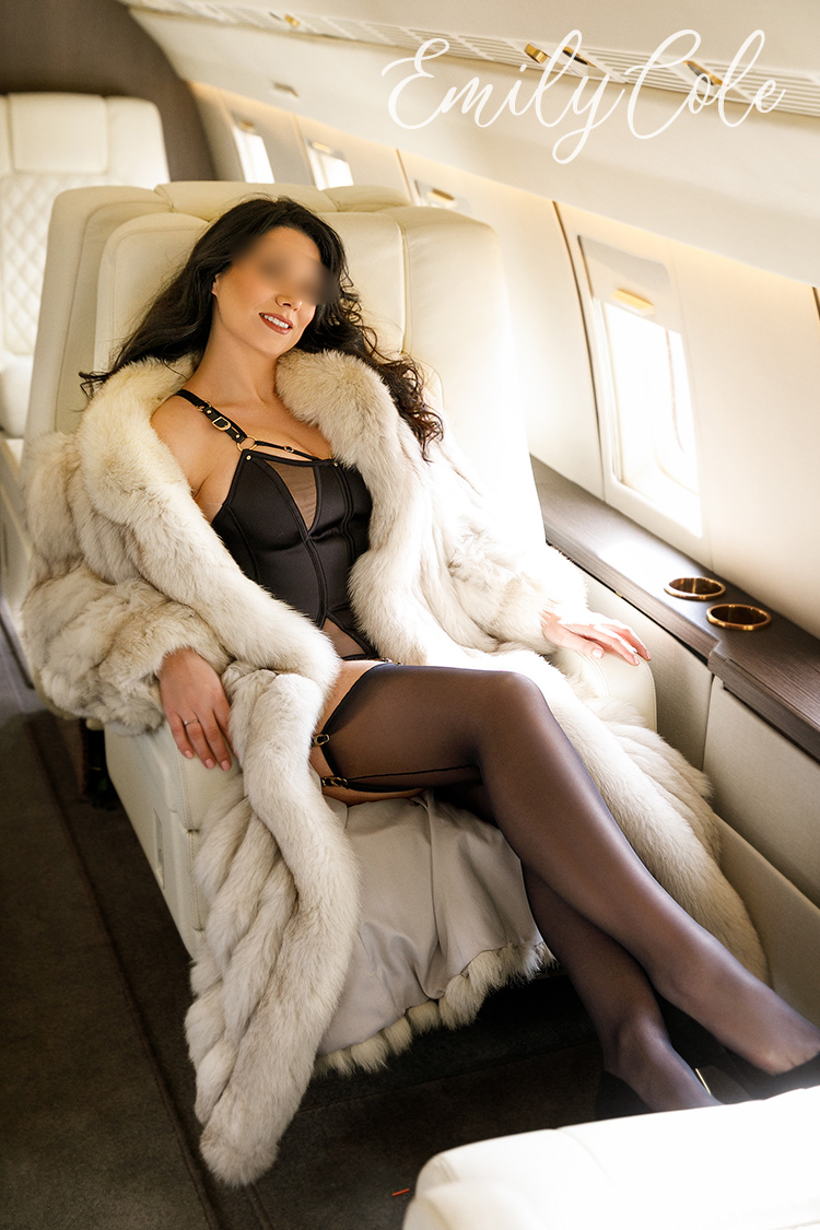 Reclining in her seat, looking glamour in a black basque and stockings.